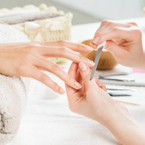 Closeup shot of a woman in a nail salon receiving a manicure by a beautician with nail file. Woman getting nail manicure. Beautician file nails to a customer. Shallow depth of field with focus on nailfile.