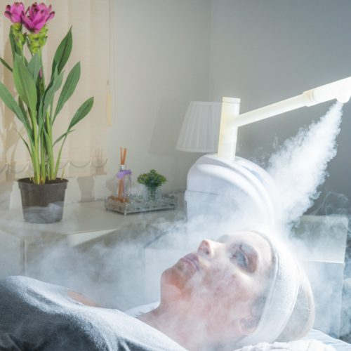 Beauty treatment of face with ozone facial steamer in beauty center. Beaultiful Blonde Girl.